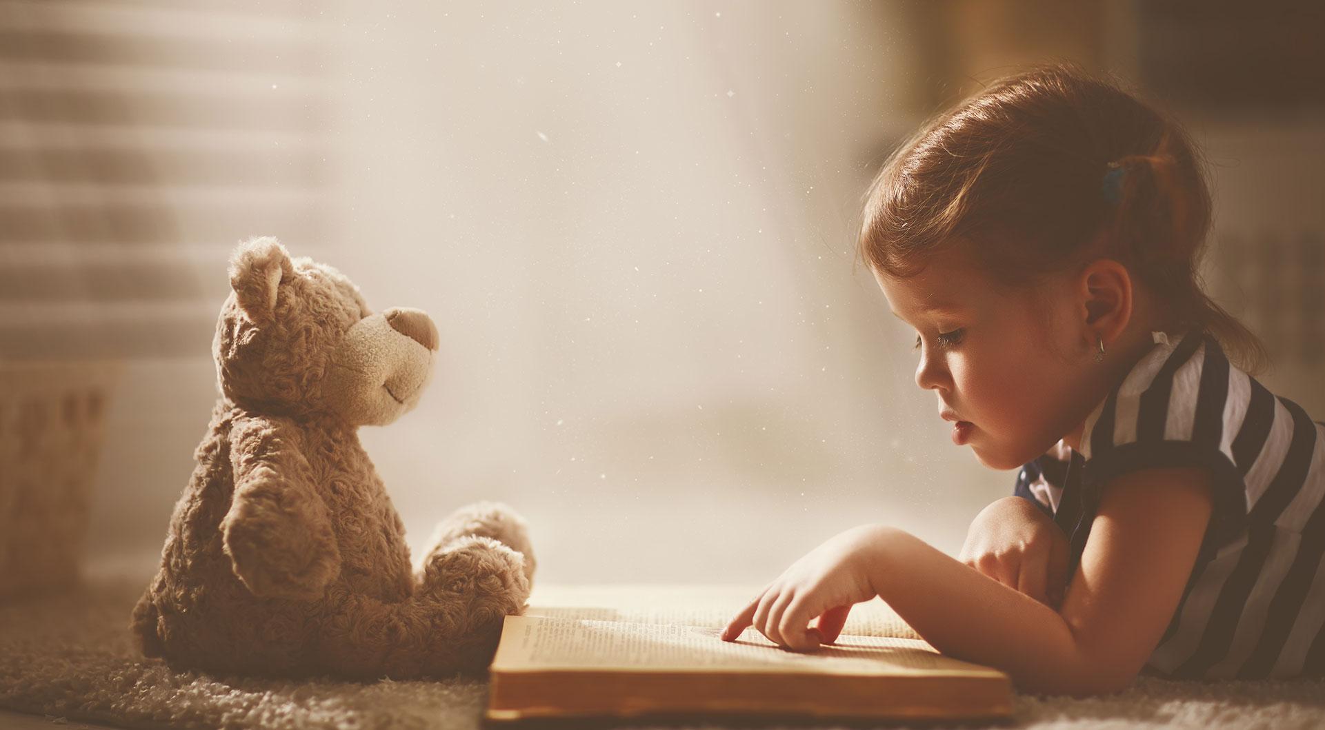 Little girl reading to her teddy bear